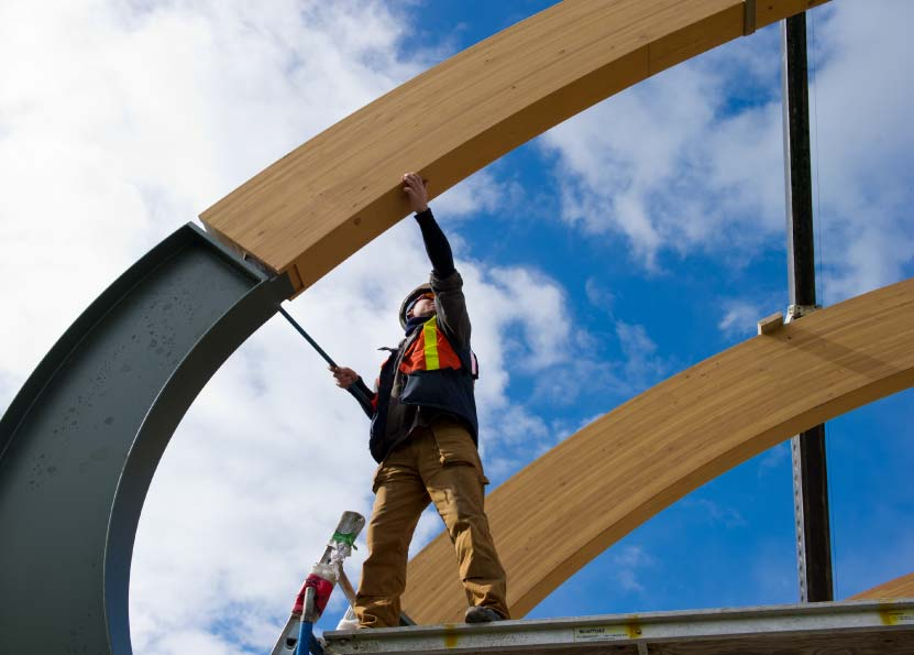 Custom fabricated structural steel integrating with curved Douglas fir glulam components.